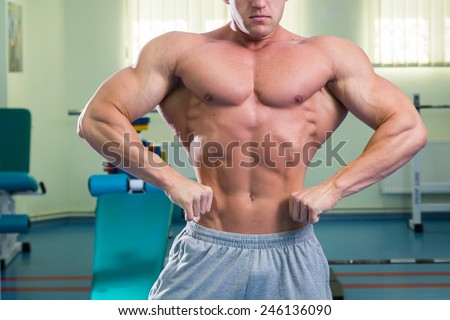 Bodybuilder showing his muscles. Muscles of the back, arms, torso. Muscular man in great shape. The concept of bodybuilding. - stock photo