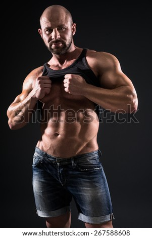 bodybuilder showing his muscles on dark background