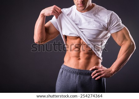 Bodybuilder showing his press. A man shows his abdominal muscles, raised his hand t-shirt. Presss, muscles, show, bodybuilding. Sports guy. - stock photo