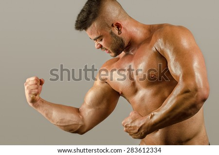 Bodybuilder topless, flexing his big biceps. Strong man with perfect abs, shoulders,biceps, triceps and chest - stock photo