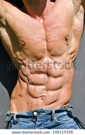 Bodybuilder torso with arms up, ripped abs and pecs with nipple piercing, wearing jeans - stock photo