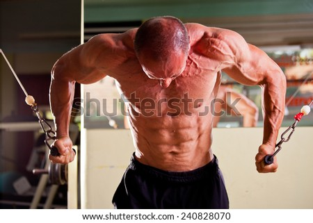 Bodybuilder training in a gym - stock photo