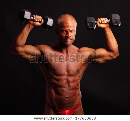 Bodybuilder training with dumbbells on black background - stock photo