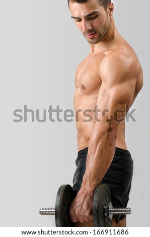 Bodybuilder training with heavy dumbbell. Strong man with perfect abs, shoulders,biceps, triceps and chest. Isolated on white background