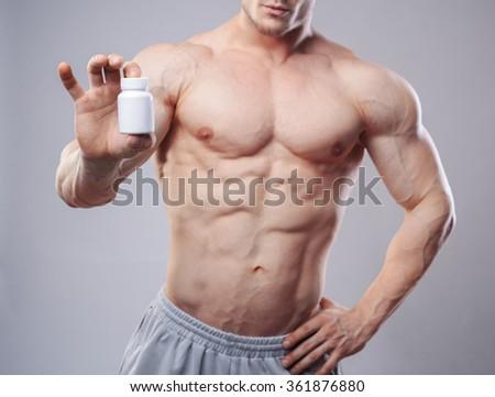 Bodybuilder with a white jar of pills on neitral background. Studio shot - stock photo