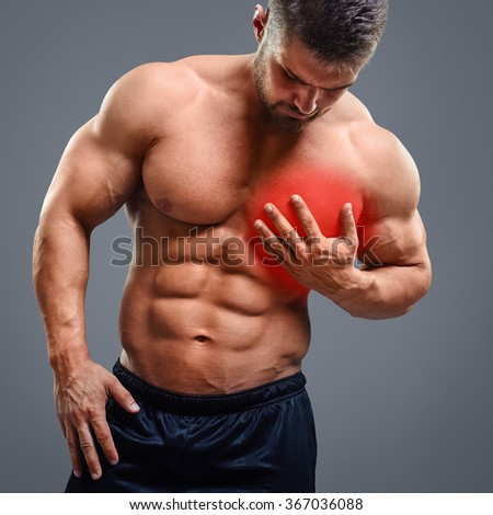 Bodybuilder with heart pain over gray background. Concept with highlighted glowing red spot. - stock photo