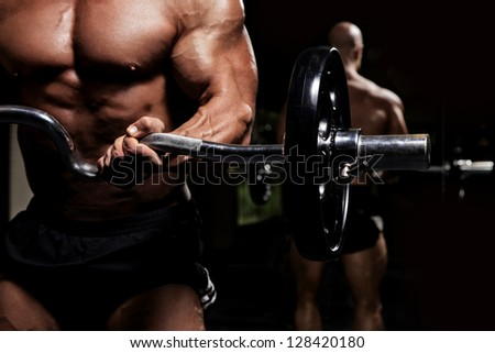 Bodybuilder working out biceps with barbell in front of mirror low key