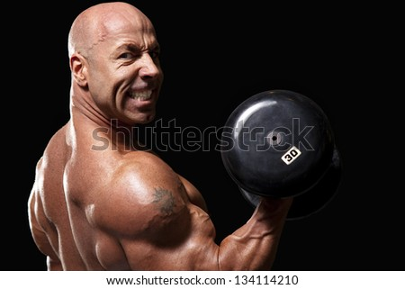 Bodybuilder working out biceps with dumbell baring teeth into camera isolated on black - stock photo