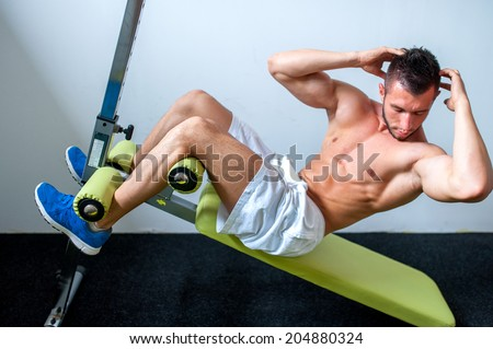 bodybuilder working the abs at the gym - stock photo
