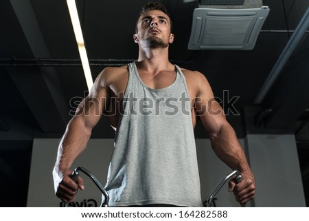 BodyBuilder Workout On Cable Machine. Standing Low Pulley Deltoids Raise - stock photo
