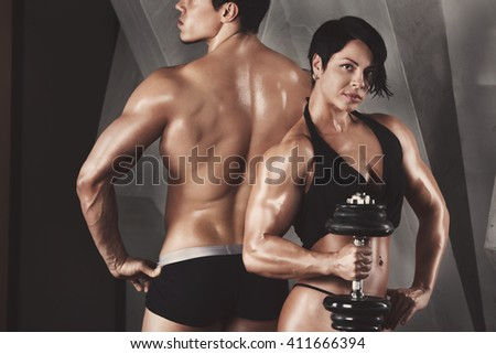 Bodybuilders. Fitness couple - woman and man with dumbbells in gym. Toning. - stock photo