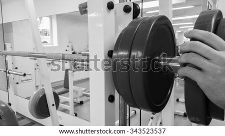 Bodybuilders performs horizontal traction on a trainer at the gym. The power to exercise the muscles of the back. Strained muscles athlete under high load. Photos for sporting magazines and websites.