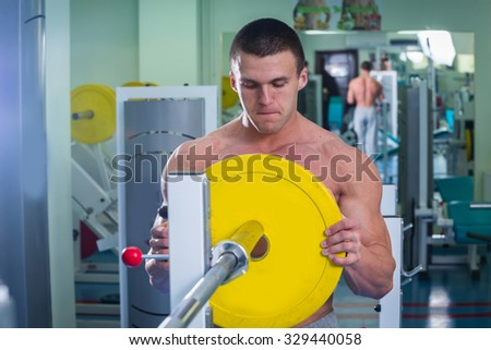 Bodybuilders preparing equipment to training. Weight gain in the simulator. Preparing for an exhausting workout. Photos for sporting magazines and websites.