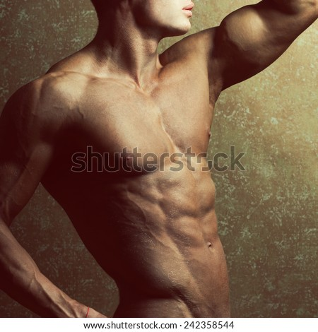 Bodybuilding and body sculpture concept. Beautiful (handsome) muscular male model with perfect body posing over golden background. Close up. Studio shot - stock photo