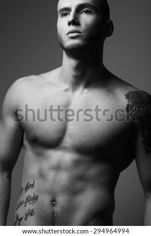 Bodybuilding and body sculpture concept. Beautiful (handsome) muscular male model with perfect body posing over gray background. Studio shot - stock photo