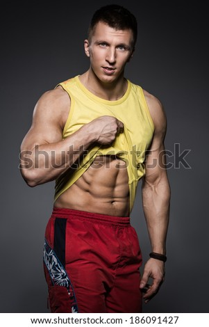Bodybuilding. Attractive man on a gray background