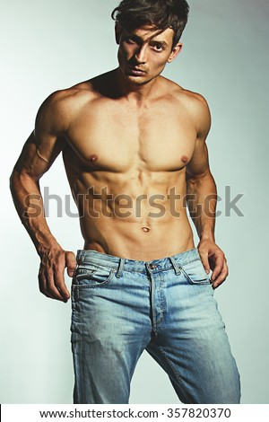 Bodybuilding, body sculpture concept. Male model with perfect body in jeans posing over grey background. Close-up. Street style.  - stock photo