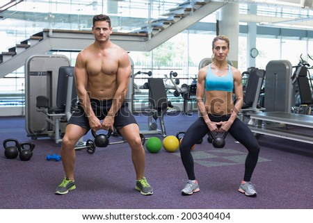 Bodybuilding man and woman lifting kettlebells in a squat at the gym - stock photo