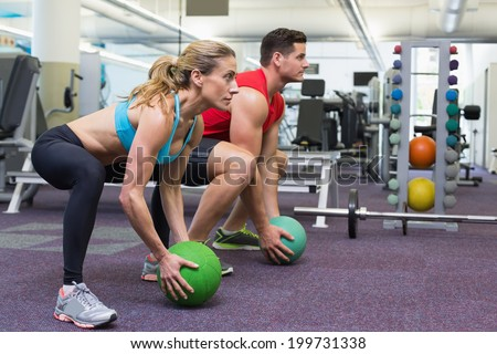 Bodybuilding man and woman lifting medicine balls doing squats at the gym - stock photo