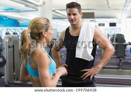 Bodybuilding man and woman talking together at the gym - stock photo