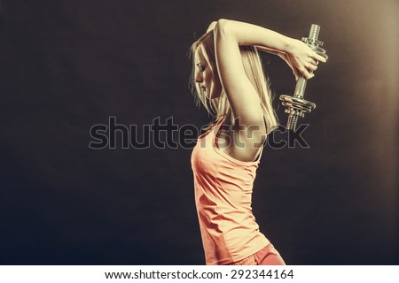 Bodybuilding. Strong fit woman exercising with dumbbells. Muscular blonde girl lifting weights studio shot on dark - stock photo