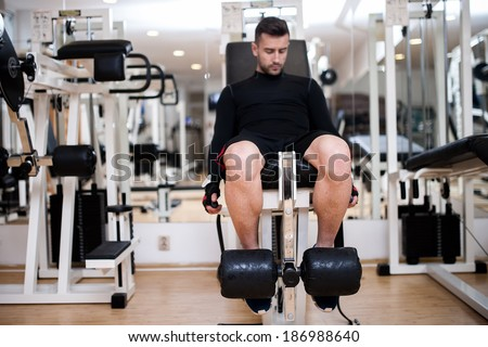 bodybulider training in gym, leg day exercises at fitness center - stock photo