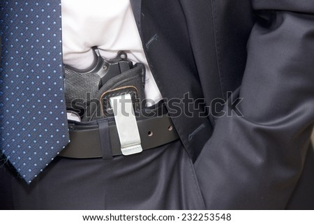 Bodyguard in a suite with a tie and a pistol - stock photo