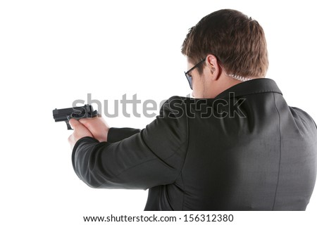 Bodyguard. Rear view of confident young man holding gun and aiming camera while standing isolated on white - stock photo