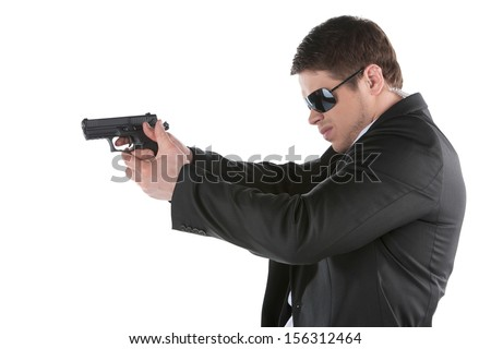 Bodyguard. Side view of confident young man holding gun and aiming camera while standing isolated on white - stock photo
