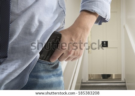 Bodyguard with gun protects client against an s water closet door background  - stock photo
