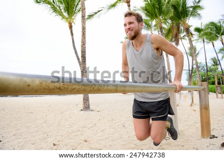Bodyweight exercises man workout on dips bars. Male adult working out triceps and biceps on horizontal bars on beach as crossfit training routine. - stock photo