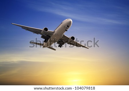 Boeing 777  landing at sunset, just before touch down, from rear. . - stock photo