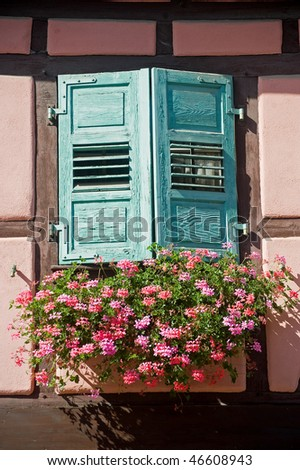 Boersch (Bas-Rhin, Alsace, France) - Exterior of pink half-timbered house: window with green shutters and red flowers