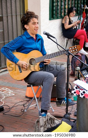 BOGOTA, COLOMBIA - APRIL 06, 2014: An unidentified musician playing guitar for money in the streets of Usaquen in Bogota Colombia. Usaquen was declared a national monument in 1987.  - stock photo