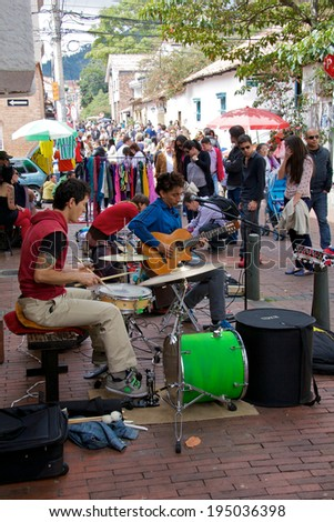 BOGOTA, COLOMBIA - APRIL 06, 2014: Unidentified musicians playing guitar for money in the streets of Usaquen in Bogota Colombia. Usaquen was declared a national monument in 1987.  - stock photo