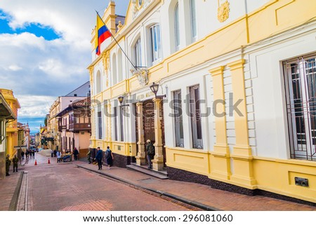 BOGOTA, COLOMBIA - FEBRUARY 25, 2015: Beautiful yellow facade of typical spanish colonial architectural bigger townhouse in charming red paved stoned street and Colombian flag hanging proudly at - stock photo