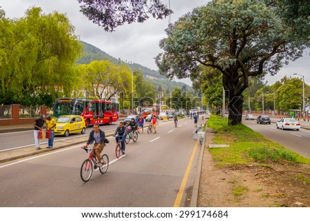 BOGOTA, COLOMBIA - FEBRUARY 9, 2015: Unidentified hispanic cyclists moving through vehicle free street with heavy traffic in opposite lane divided by trees Candelaria area Bogota, Colombia