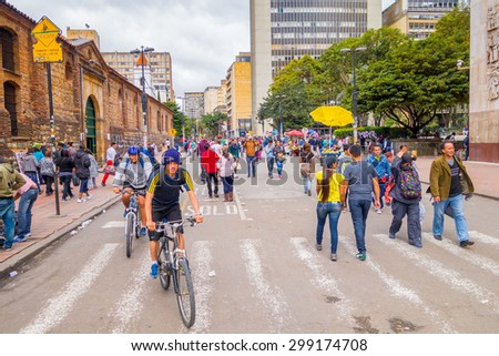 BOGOTA, COLOMBIA - FEBRUARY 9, 2015: Unidentified hispanic pedestrians and cyclists moving through city street Candelaria area Bogota - stock photo