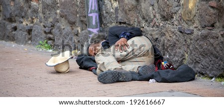 BOGOTA, COLOMBIA - MAY 06, 2014: An unidentified homeless man sleeping in the streets of Bogota Colombia. The World Bank estimates that one in three people live below the poverty line in Colombia.