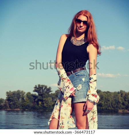 Bohemian fashion girl in kimono and blue denim shorts. Red haired young woman in summer outfit. Portrait of a beautiful girl standing by the river, enjoying a warm summer day in the nature.