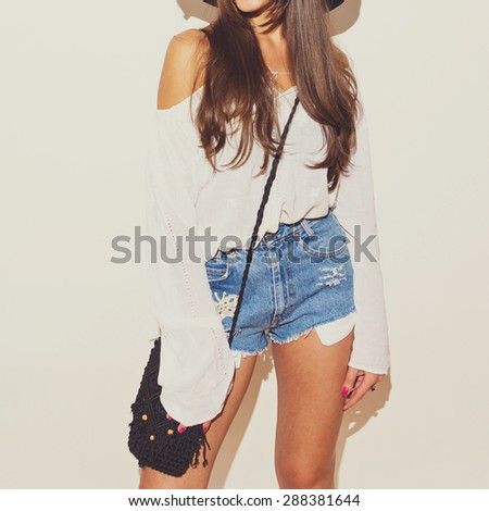 Bohemian fashion girl in white long sleeve blouse and blue denim shorts with crochet butterfly and black crochet purse. Brunette young woman in summer outfit.  - stock photo