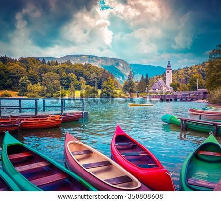 Bohinj Lake with boats and Church of St John the Baptist, Triglav National Park, Julian Alps, Slovenia. Instagram toning. - stock photo