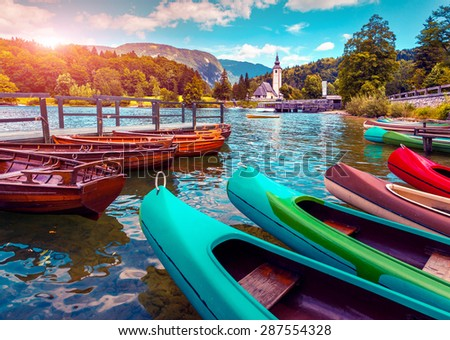 Bohinj Lake with boats and Church of St John the Baptist, Triglav National Park, Slovenia. Instagram toning - stock photo
