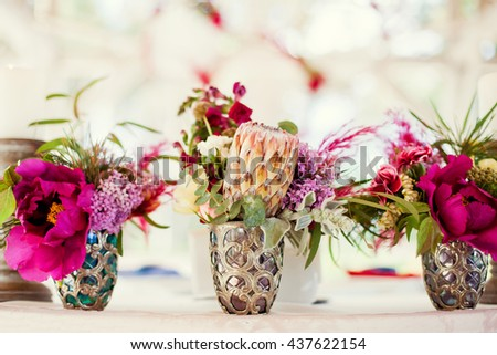 boho composition with protea, lilac and feathers