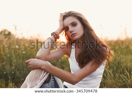 Boho lifestyle. Fashion portrait of beautiful young pretty girl with hippie outfit outdoors in the field at sunset. Soft warm vintage color tone. Artsy Bohemian Style. Horizontal. Eye contact - stock photo