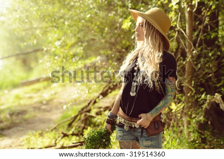 Boho style fashion. Beautiful young woman wearing boho style clothes posing in the rays of the evening sun, sunset.  - stock photo
