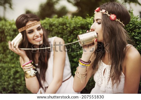 Boho women talking by tin can phone - stock photo