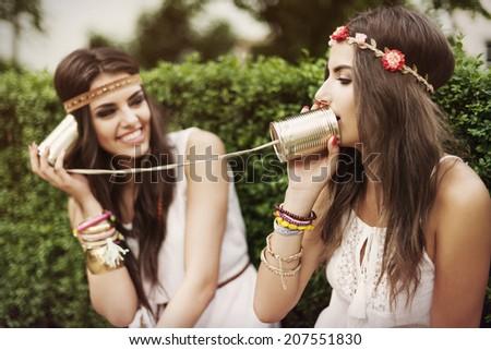 Boho women talking by tin can phone - stock photo