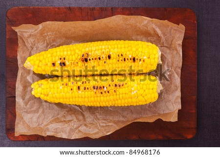 Boiled and roasted golden corn on a piece of baking paper. Culinary healthy vegetable. - stock photo