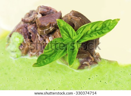 Boiled beef shin with young fresh green pea sauce decorated basil leaf - stock photo